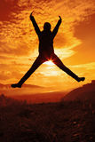 Happy young woman jumping at the sunset Stock Images