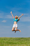 The happy young woman jumps in the field Stock Photo