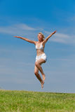 The happy young woman jumps in the field Stock Photos