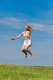 The happy young woman jumps in the field Stock Images