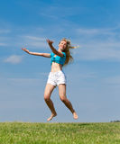 The happy young woman jumps in the field Royalty Free Stock Photo