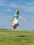 Happy young woman jumps in the field Stock Image