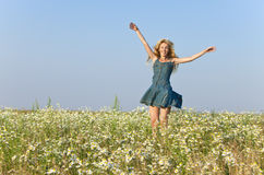 The happy young woman jumps in the field  of camomiles Royalty Free Stock Photo