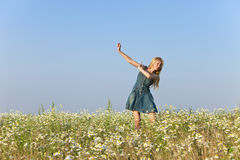 The happy young woman jumps in the field  of camomiles Royalty Free Stock Photography