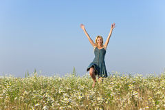 The happy young woman jumps in the field  of camomiles Stock Images