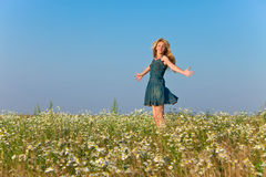 The happy young woman jumps in the field  of camomiles.Portrait in a sunny day Royalty Free Stock Photography