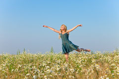 The happy young woman jumps in the field  of camomiles in a sunny day Stock Images