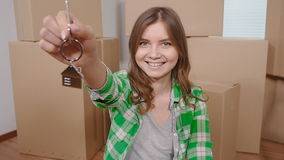 Happy young woman with a key from a new apartment