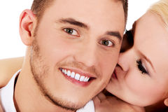 Happy young woman kissing her boyfriend Royalty Free Stock Photos