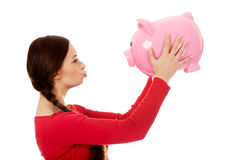 Happy young woman kissing a piggybank Royalty Free Stock Photography