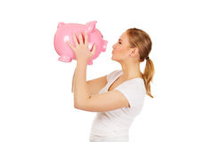 Happy young woman kissing a piggybank Stock Image