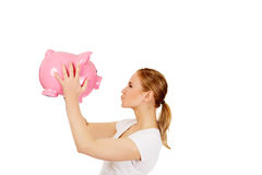 Happy young woman kissing a piggybank Royalty Free Stock Images