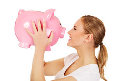 Happy young woman kissing a piggybank Royalty Free Stock Photo