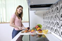 Happy young  woman in kitchen Stock Photos