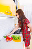 Happy young woman in the kitchen. One happy young woman in the kitchen preparing a salad from vegetables Stock Photography