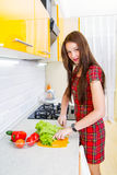 Happy young woman in the kitchen. One happy young woman in the kitchen preparing a salad from vegetables Royalty Free Stock Images