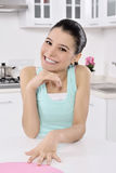Happy young woman in the kitchen stock photos