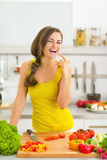 Happy young woman in kitchen licking fingers Stock Photos