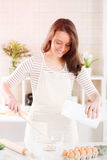 Happy young woman in the kitchen. Happy young woman making dough in the kitchen Stock Photography