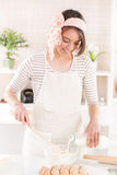 Happy young woman in the kitchen. Happy young woman making dough in the kitchen Royalty Free Stock Image