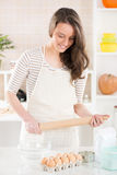 Happy young woman in the kitchen. With Rolling Pin Stock Image