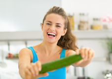 Happy young woman in kitchen showing cucumber Stock Photography