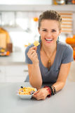 Happy young woman in kitchen showing halloween boo chips treats Royalty Free Stock Image