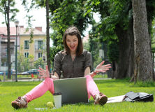 Happy Young Woman on a Laptop. Happy young woman in front of a latop siting on grass outside in an urban park Stock Images