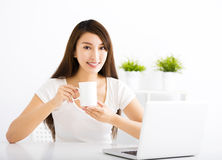 Happy young woman with laptop in living room Stock Images