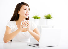 Happy young woman with laptop in living room Royalty Free Stock Photography