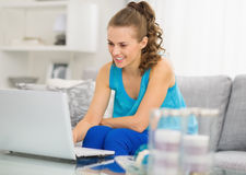 Happy young woman with laptop in living room Stock Photos