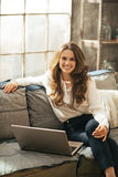 Happy young woman with laptop in loft apartment Stock Photos
