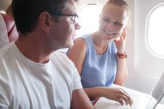Happy young and woman with laptop in plane royalty free stock photos
