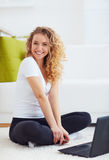 Happy young woman with laptop, sitting on carpet at home Royalty Free Stock Photos