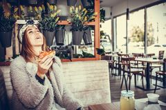 Happy young woman laughing while eating a slice of pizza Royalty Free Stock Images