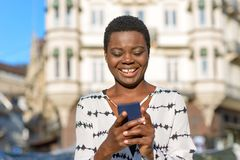 Happy young woman laughing at her mobile phone stock images