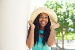 Happy young woman laughing and holding sun hat Stock Photo