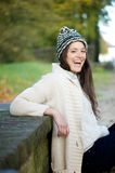 Happy young woman laughing outdoors with sweater and hat Stock Photography