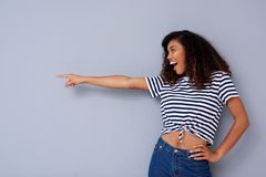 Happy young woman laughing and pointing at copy space. Portrait of happy young woman laughing and pointing at copy space Stock Images