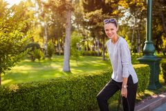 Happy young woman laughing posing in summer park. College student with bag walking and having fun stock image