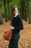 Happy young woman laughing and walking outdoors with bag Royalty Free Stock Photography