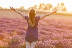 Happy young woman on lavender field at sunset Royalty Free Stock Photo