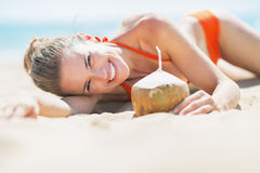 Happy young woman laying on beach with coconut Royalty Free Stock Photo