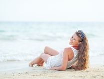 Happy young woman laying on beach in the evening Royalty Free Stock Images