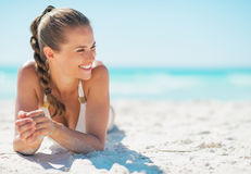 Happy young woman laying on beach Stock Image