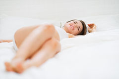 Happy young woman laying on bed Royalty Free Stock Photos