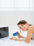 Happy young woman laying on bed with laptop Royalty Free Stock Photo