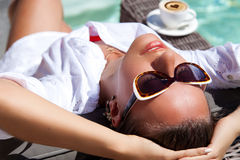 Happy young woman laying on chaise-longue poolside Royalty Free Stock Images