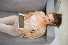 Happy young woman laying on couch with tablet pc Stock Photo