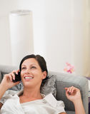 Happy woman laying on divan and talking cell phone Stock Images